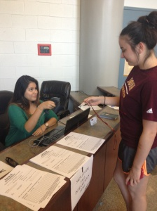 Joselyn Mancilla scanning Jess Martin's ID before entering the Hynes Athletic Center